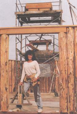 Dorothy Ainsworth is shown holding the jig that helped her mark the birdsmouth notches on each rafter.  The cupola frame rests atop the scaffolding behind her.