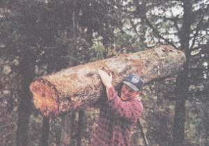 Kirt carries a 500-lb. log to the truck