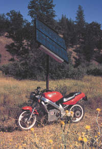Solar panels recharge an electric motorcycle miles from grid power.