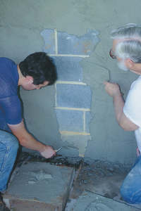 Use a trowel to smear the parget material over the surface of the dampened cement blocks. Lap over the final part of the wet mortar each time you apply another trowel-ful of mortar.