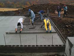Crew pours the slab floor. Concrete is pumped via the hose.