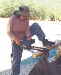 Dorothy uses her electric chainsaw to shave a tenon.