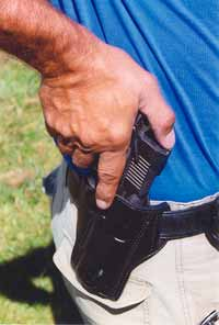 Thumb holds back hammer of cocked and locked Kimber .45, and trigger finger is extended as author slips the pistol into Josh Bulman belt holster. This is the safest holstering technique.