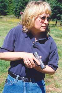 Ace firearms instructor Gila Hayes demonstrates low ready with Kahr 9mm. Note trigger finger safely 'registered' on frame, muzzle at 45 degrees, gun where she can still see it in lower periphery of vision without having to lower her head.