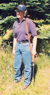 Gila Hayes demonstrates African carry. Sling is over weak side shoulder, muzzle forward and down. Note position of left hand, ready to snap the rifle to her right shoulder at a moment's notice.
