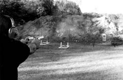 Author practices for 'gunfighter' class at a Cowboy Action Match, which requires a revolver in each hand fired alternately. Taurus Gaucho .45 in right hand has just fired and hit the steel plate at right (note hammer down), while .38 caliber counterpart in left hand is about to be fired (hammer still cocked).