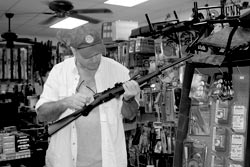 Steve Sager is a Master competitive shooter who has learned to appreciate the inexpensive Mossberg Plinker .22 rifle as a 'best buy.' Here, he checks out a used specimen at Daddy's Gun Shop in Mayo, Florida.