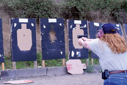 "Kathy Jackson, author of articles, books, and the great www.corneredcat.com website, runs to slidelock with the last shot from her Glock 19, and her aggressive stance keeps the muzzle on target in ""follow-through."" Photo from an LFI class at Firearms Academy of Seattle."