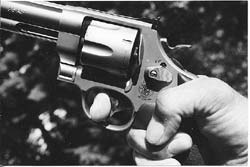 High hand grip, thumb curled down for strength, index finger at distal joint on trigger for maximum leverage. This is the grasp author used to win IDPA NH State Championship in 2003 with this stock service revolver, S&W's .45 caliber Model 625.