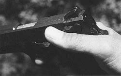 With a slide mounted safety as on S&W Model 457 compact .45, shown, author prefers this grasp, with thumb at upward angle to guarantee release of safety catch.