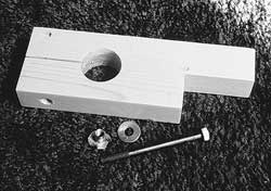 The parts making up the vise mount. Holes have been drilled in the blank and the expansion slot has been cut. The bolt, Tee nut, and washer are ready to be installed.