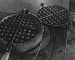 The two pieces of this cast iron waffle iron are set together on the ring after you have added your batter. The iron is oiled and heated before the batter is added.