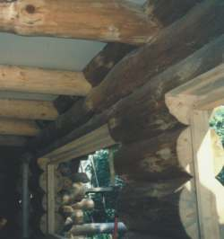Photo shows window framing nailed onto recessed, slotted 2x4s; note space above to allow for settling.