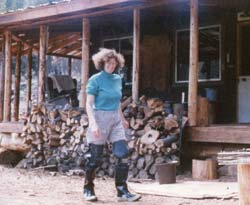 Lenie, in wading boots, walks by the front porch made from small firs I retrieved from a logging slash pile. Lenie took over all the business details, including the magazine's finances, freeing me to write and edit.