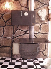 A shepherd or camp stove offered by Cabela's catalog. It has a detachable shelf on the right, detachable five-gallon hot water tank on the left, and an oven sitting above the stove body. The whole thing breaks down and is portable. It cooks very nicely, too. Costs about $500 for all components, excluding stove pipes, and it can be bought piecemeal. The light in the upper left-hand photo is a lit oil lamp, placed to give light when using the stove.