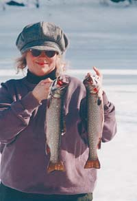 Linda Gabris with a couple of great trout for supper. Ice fishing is a delightful way to cash in on winter fun.