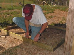 Husband Roy makes certain frames for exterior half-walls are squared before placing them between the 4 x 4 posts.