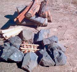 The makings of a fire: Tinder and kindling in the fire ring; extra kindling and starter logs set outside the fire ring; and some firewood.