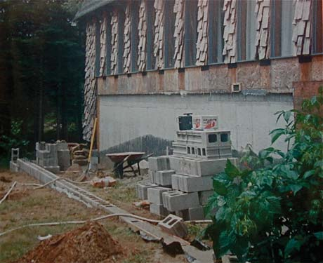 Early stages of construction. Foundation wall rises above ground and house wall has been stripped to the sheathing. Note the large area of the house foundation that will be painted green for solar gain.