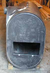 Front view of large heater showing attachment of 55-gallon drum section and exhaust pipe. This arrangement gives more volume in fire chamber and allows direct 'plug-in' to chimney.