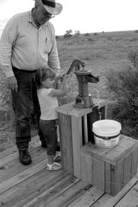Roy and granddaughter, Annie Acosta, pump water from the cistern.