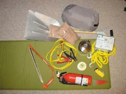 Some of the things in my car: Insulated ground pad, sleeping bag, jumper cables, tow strap, fire extinguisher, first aid kit, flashlight, candle and matches, ice scraper, shovel, a pot for melting snow or storing water, and MREs.