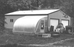 The author's greenhouse is attached to his garage. In cold weather heat from a wood stove inside also heats the greenhouse through an open garage window.