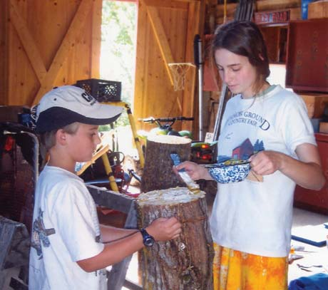 Kayla and Kane paint beeswax on a log to cover Shiitake mushroom plugs.