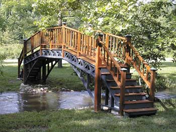 Our homemade footbridge leans toward the 'Asian' design because of the shallow banks. Whether you are  building over a creek or a pond, the height does not have to be more than a few feet above water level.
