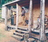 Bill Ingles and Jon Stram, on the front porch of the cabin, plane 1 inch by 6 inch by 8 foot red cedar boards for the cabin's interior.