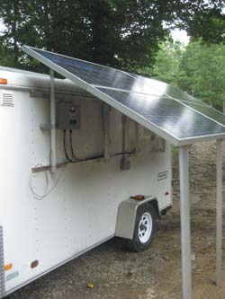 Raised solar array showing side-mounted array combiner box and GFI duplex 120 VAC outlet box.