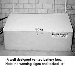 A well-designed vented battery box. Note the warning signs and locked lid.