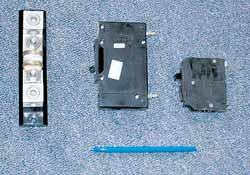 Catastrophic battery DC safety fuse on left. Note much larger size of 15-amp DC circuit breaker (center) compared to a standard 15-amp AC circuit breaker (right).