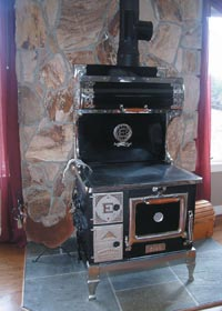 This modern version of an antique wood cook stove can fry bacon, eggs, and bake hot biscuits while providing a warm kitchen.