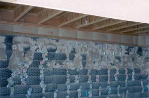 Fig. 3 - Tire wall with cans behind stucco netting, with some of the larger voids filled with mud.