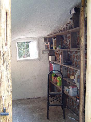 The interior of the shed has been plastered with gypsum, whitewashed, and outfitted with shelves.