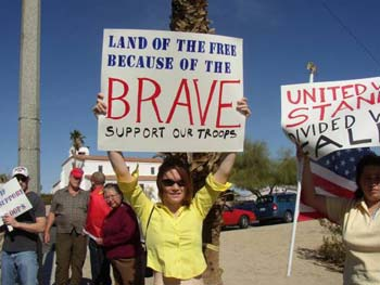 Annie Tuttle, wife of Marine Corps Pfc Erik Tuttle, who is in Kuwait, holds a sign during a spontaneous pro-America rally to counter peace activists demonstrating in 29 Palms, California. She said the overwhelming majority of people driving by honked for the counter rally, not for the peace activists.