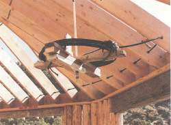 This is the steel cable that keeps the weight of the roof over the uprights by preventing the rafter ends from spreading outward. This cable eliminates the need for a centerpost and allows an open, vaulted ceiling.