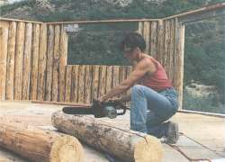 'Flatting' a log to create a flat, even side. Here, Dorothy is making one of many shallow kerf cuts down to snapped chalk lines. Later she cut off the pieces formed by these cuts to create the flat side.
