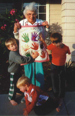 Grandma Kathy Myers shows off her wall hanging with the help of her grandchildren, from left, Robby, Sammy, and Jacob Duffy.