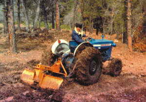 Hubert Burris on a Ford 2000 tractor with blade attached