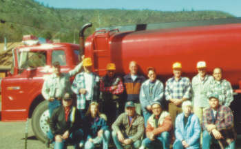 Some of the volunteers pose with the water tanker (Frank Tickle photo).