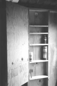 Lockable shelf constructed between wall studs in the tool shed