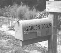 his old mailbox is posted at the entrance of our garden, keeping hand tools ready at all times.