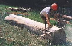 Milling a board with a chainsaw lumber-maker.
