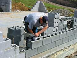 Mason Ron Latour lays up 700 blocks in Eric's stepped-wall basement.