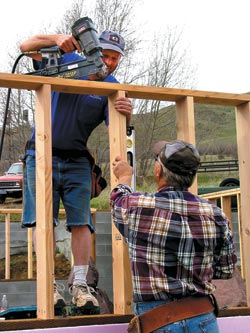 Ron and Eric build a pony wall as a team. Ron plumbs the stud with his level, and Eric nails the top plate to it as they go along.