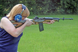 "5'0"" Gail Pepin is about to put some .223 fire dead center into the target with a Ruger AC556 machine gun, the selective fire version of the Ruger Mini-14. (Note selector switch at rear of receiver.) Aggressive forward stance makes it possible for small women to control hard-kicking guns."