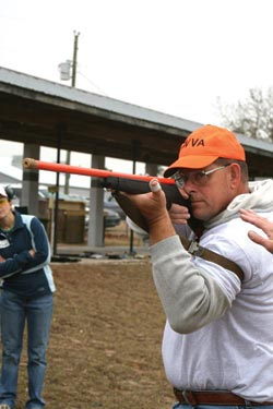 Orange hat connotes instructor-in-training status for Mike Larney, here using an orange dummy rifle to demonstrate use of loop sling to stabilize hold in offhand (standing) position.
