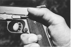 Traditional grasp of the .45 autoloader. Thumb rests on manual safety, pad of index finger is in contact with trigger.